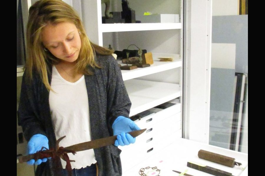 Shelbie McCormack examines a Vietnamese ceremonial dagger while cataloging objects for Bates College Museum of Art