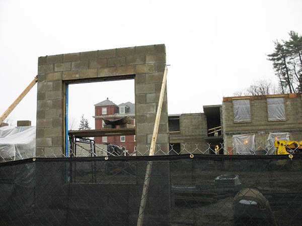 In this Dec. 14 image of the new student housing, 101-year-old Rand Hall is framed through an opening in a freestanding section of wall. This wall was created as a model of proper construction techniques for the actual building. (Doug Hubley/Bates College)