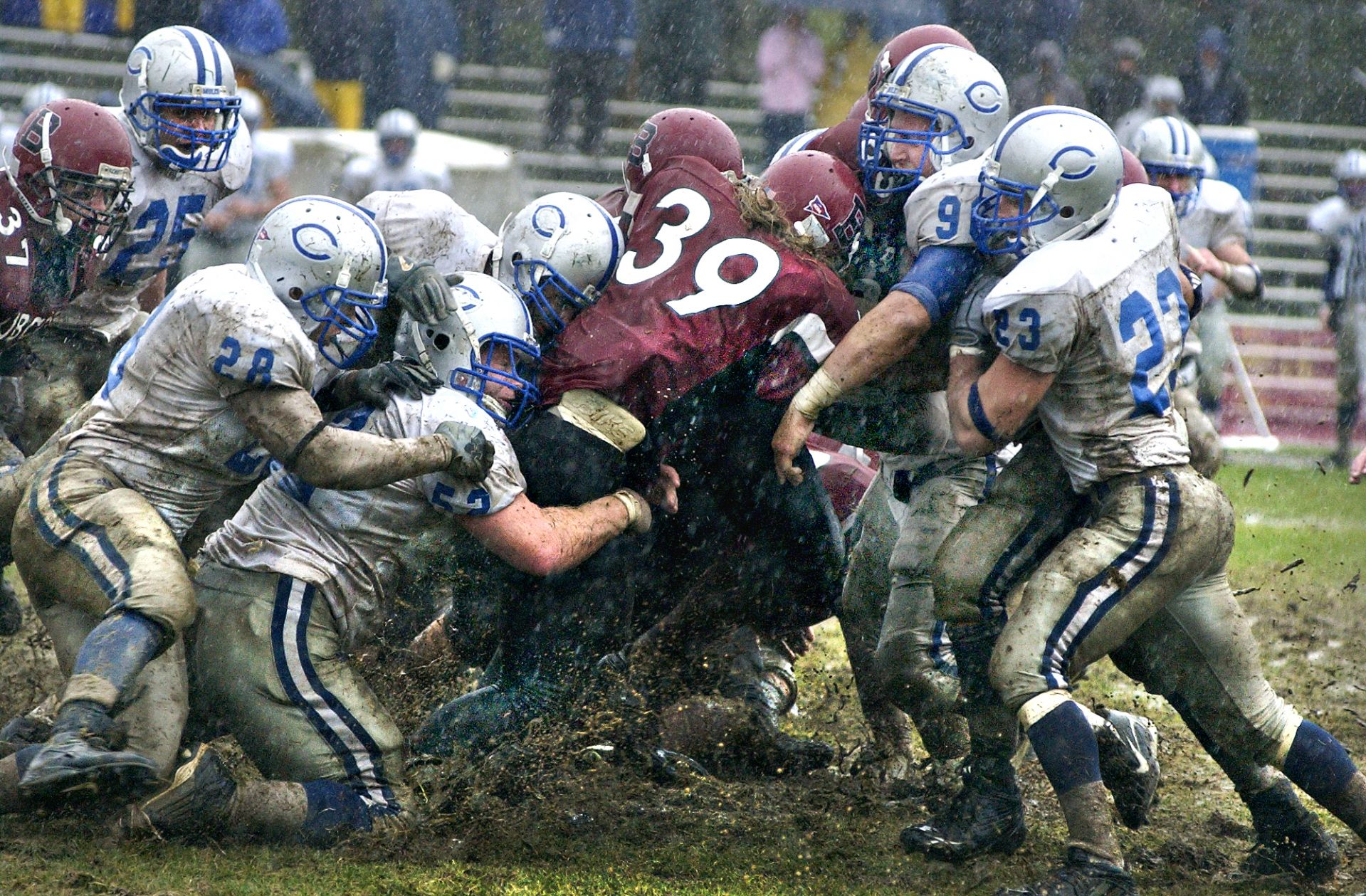 Later featured in Sports Illustrated, this iconic Bates photograph shows Jamie Walker '07 of Needham, Mass., moving a pile of Colby Mule defenders during a game at Garcelon Field on Oct. 28, 2006. (Daryn Slover for Bates College)