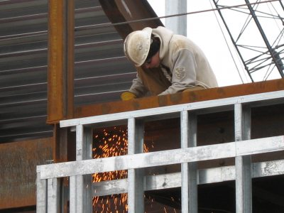 A welder makes sparks on the new Commons. (Doug Hubley/Bates College)