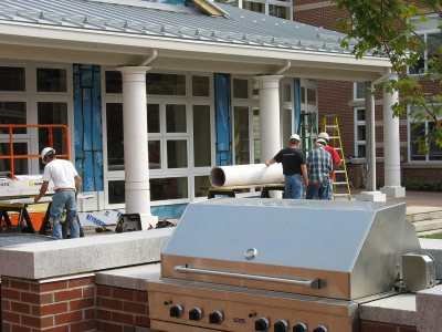 Setting up columns on the porch outside Frank's Lounge. (Doug Hubley/Bates College)