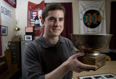 Bates debater Geoff Shaughnessy '09 of Hanover, N.H., poses in the Brooks Quimby Debate Council's storied practice room on the second floor of Pettigrew Hall. The trophy bowl he holds is a first place award for Bates from a tournament held at MIT in 1981, five years before Shaughnessy's birth. The croquet mallet he holds sometimes substitutes for a gavel during team practices. The traditional mallets have disappeared.