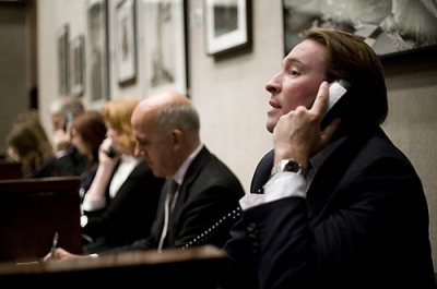 "Joshua Holdeman '93 joined Christie's New York as international director and head of the firm's New York photographs department and of Christie's New York 20th-century decorative arts department. He serves in both a managerial and international business-getting role, with focus on pursuing high-value property and single-owner collections.  Shown here working the phones with clients at the two-day New York  auction of ""Icons of Glamour and Style: The Constantiner Collection,"" at 20 Rockefeller Plaza. The collection features an extensive range of work of Helmut Newton and various other acclaimed photographers whose images portray high fashion models and glamourous celebrities (many of Marilyn Monroe), along with other assorted images. Also shown at a auction for Tiffany's antiquities.  Auctioneer at Tiffany event and for the first Constantiner sale is Philippe Garner, international head of the international photography department, and Andrea Fiuczynski, in the second sale. Also shown, collector Leon Constantiner (black glasses, bald head) and art handler William Gregory."