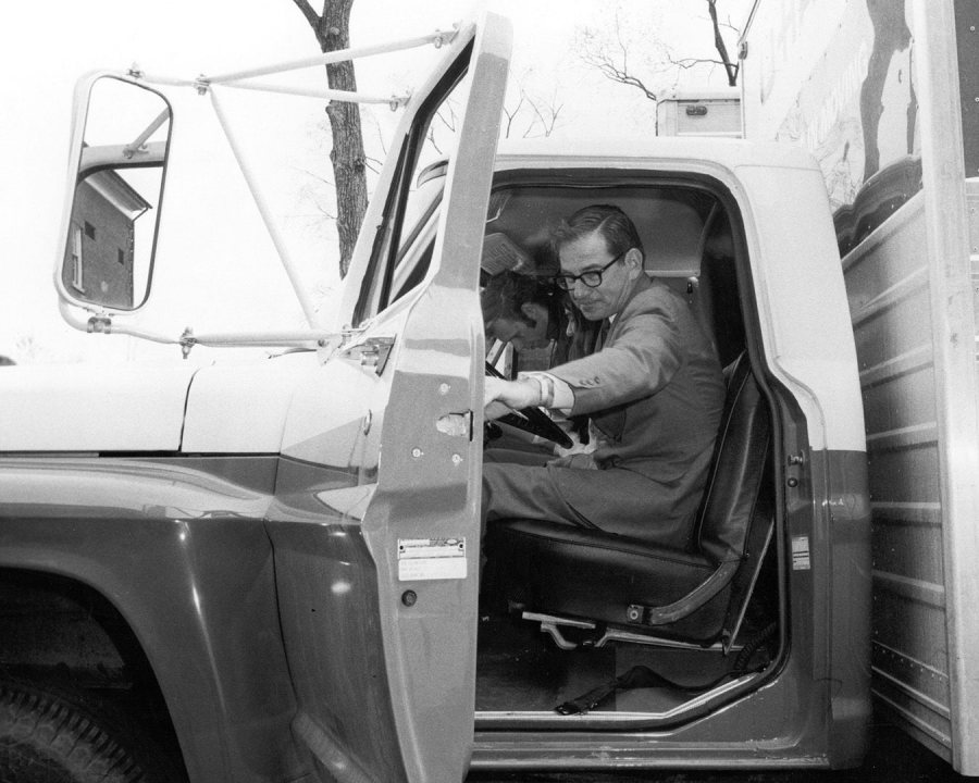 In May 1970, Bates President Thomas Hedley Reynolds climbs into the cab of a donated U-Haul truck to lead Bates students on a strike project: a downtown Lewiston trash cleanup. (Muskie Archives and Special Collections Library)