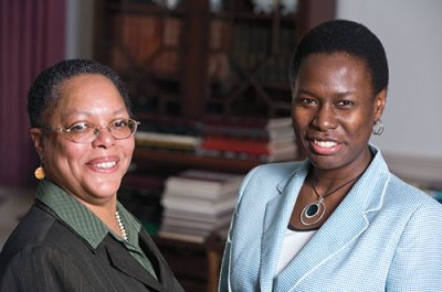 "Carmita McCoy (green suit with glasses) and Marylyn Scott (checked blue suit) pose in Lindholm House. They share a position, the Director of Multicultural Recruitment and Associate Dean for Student Transition, known as ""swing dean."""