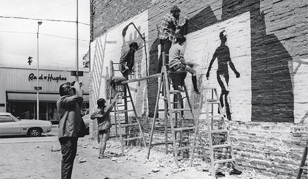 Students paint the Lisbon Street mural in 1971 as an unidentified man films the work.