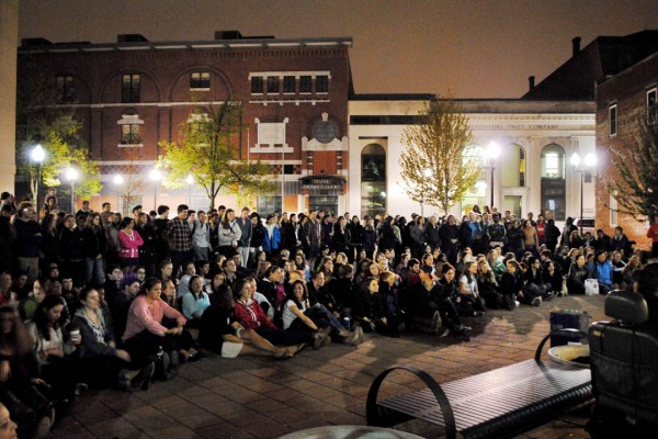 "A Bates crowd at the Courthouse Plaza on Lisbon Street listens to the all-college a cappella performance that concluded the 2012 ""College Night in Town."" Photograph by Michael Pasek '12."