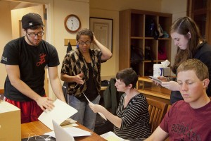 "Students in the Short Term course ""Making African American History: Preserving the Archives of the Portland NAACP"" examine documents during a work session at the University of Southern Maine. From left: Joncarl Hersey '12, Tasheana Dukuly '€™12, professor Mollie Godfrey, Munroe Graham '€™13, Brad Reynolds '€™14. Photograph by Phyllis Graber Jensen/Bates College."