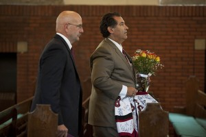 John Pappas, father of Troy '16, leaves the College Chapel at the end of the Oct. 11 memorial service, followed by head football coach Mark Harriman. Pappas holds Troy's jersey, signed by his teammates, and a floral arrangement from the service. Photograph by Phyllis Graber Jensen/Bates College.