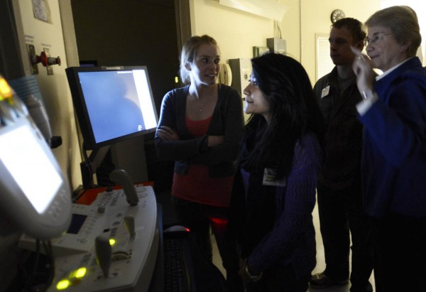 Director of radiology at St. Mary's Regional Medical Center, Donna Knightly demonstrates an X-ray machine for Samantha Forrest '13, Raisa Sharmin '13, and Keyan Riddell '16. Photograph by Michael Bradley/Bates College.