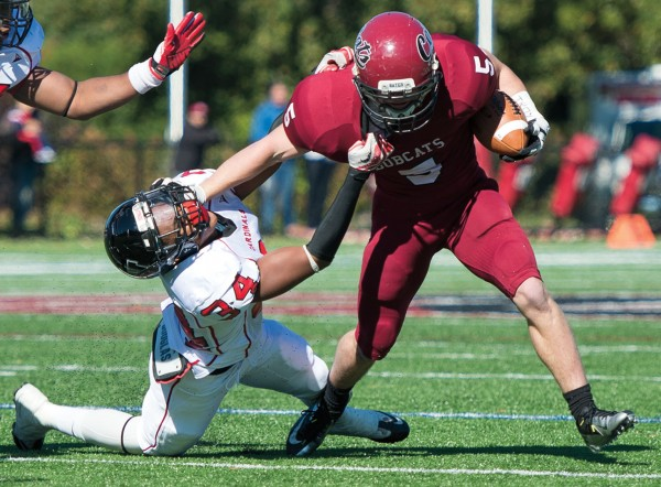 Slot receiver Mac Jackson '15 of Hood River, Ore., stiff-arms a Wesleyan defender — emblematic of coach Mark Harriman's statement that the Bobcats in 2012 were physically on par with any NESCAC team. Photograph by Mike Bradley