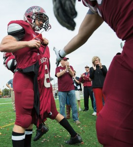 Bates players touch the No. 8 jersey of the late Troy Pappas '16 while entering Garcelon Field for the Williams game, as Pappas' uncle Gary Blackwell (Bates shirt) and President Spencer (black coat) show their support. Photograph by Mike Bradley