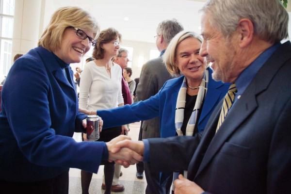 A historic moment as Interim President Nancy Cable introduces the president-elect to President Emeritus Donald Harward in Perry Atrium during a celebration of new appointments to Bates faculty professorships. Photograph by Phyllis Graber Jensen/Bates College.