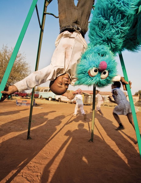 Child with Sesame Street character, Soweto, South Africa, for a Sesame Workshop report on international programs. Photograph by Ryan Heffernan '05