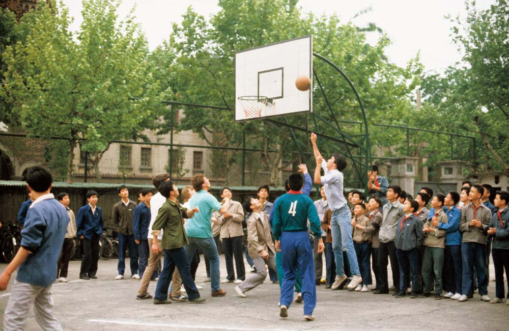 Bates student and Chinese youths play basketball in 1981. While here the Americans overall seem taller than their counterparts, socioeconomic development since then has meant the average height of an urban Chinese male has increased by nearly three inches. Photograph by Steve Stone '83.