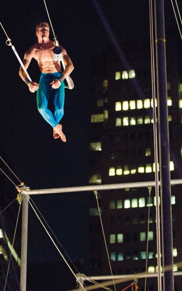 At the apogee of an upswing, Jones is poised to catch the next student flying his way at the South Street Seaport location of the Trapeze School New York.  Photograph by Phyllis Graber Jensen