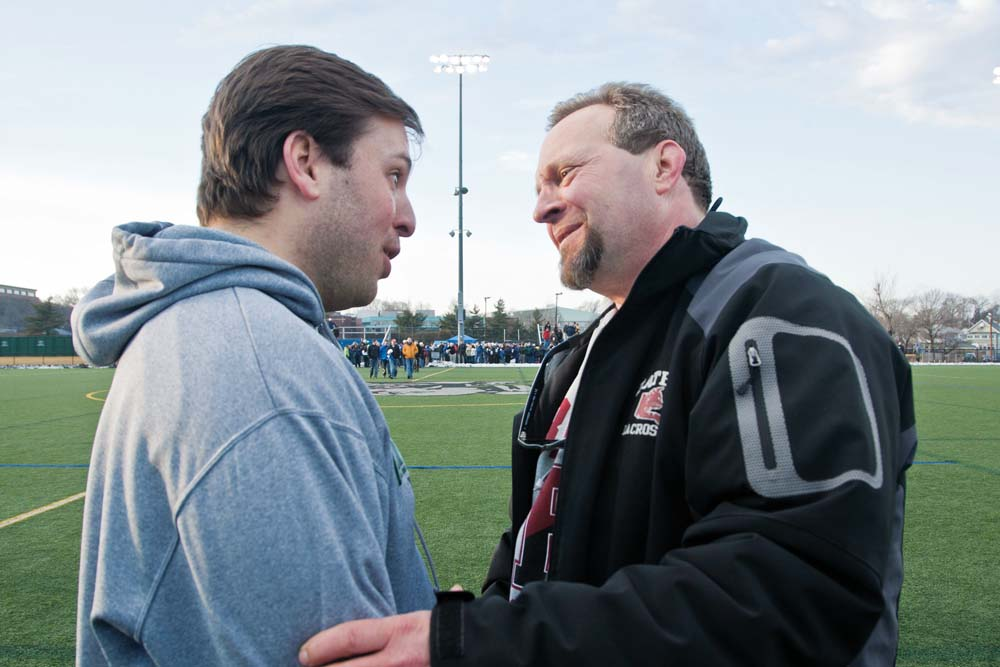 With the fierce game competition concluded, Bates coach Peter Lasagna and his former player, Skidmore coach Jack Sandler '02, each with his own deep connection to Morgan McDuffee, come together for an embrace. Photograph by Phyllis Graber Jensen/Bates