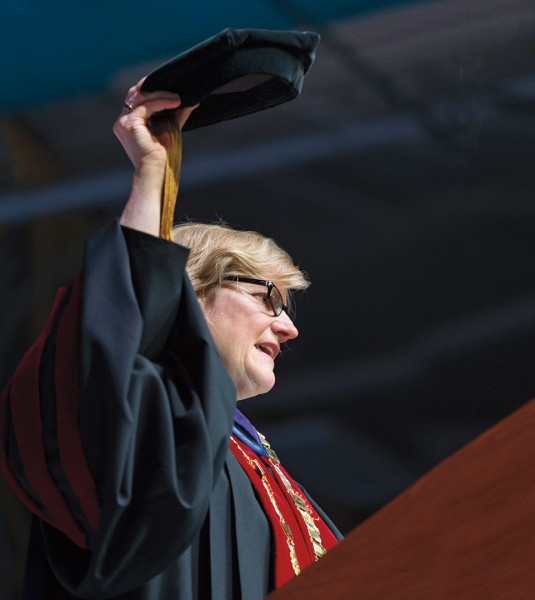 A poignant moment during the installation: Clayton Spencer hoists her academic cap, the same one that her father, Samuel Reid Spencer Jr., now 93, wore as president of Mary Baldwin College and Davidson College. Photograph by Mike Bradley