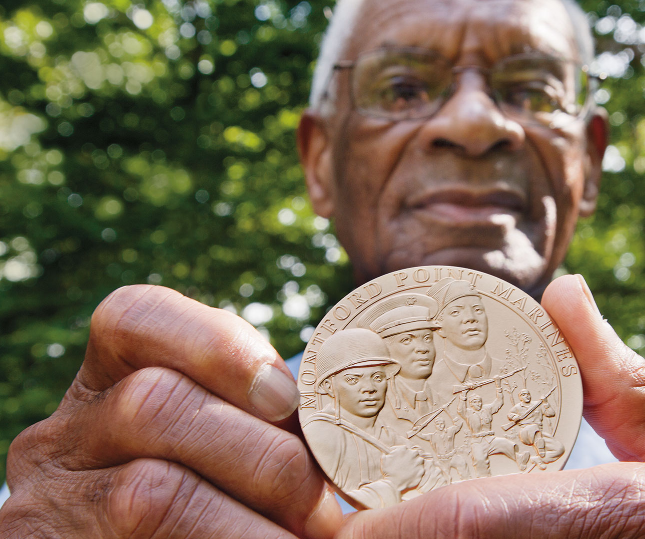 Shown at his Manchester Center, Vt., home in September 2012, Nathaniel Boone '52 displays the Congressional Gold Medal he received for his service as a Montford Point Marine.  Photograph by Phyllis Graber Jensen