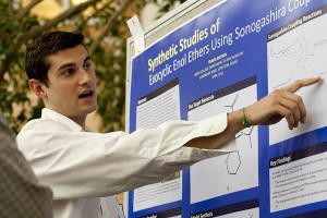 "Travis Brown '11 of East Greenwich, R.I., explains his chemistry poster, ""The Synthesis of Exocyclic Enol Ethers Using Sonogashira Couling,"" at the 2011 Mount David Summit. Photograph by Phyllis Graber Jensen/Bates College."