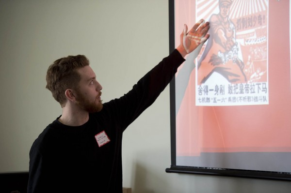Clay Baldo '13 explains a Chinese political poster during the Mount David Summit. Photograph by Michael Bradley/Bates College College.