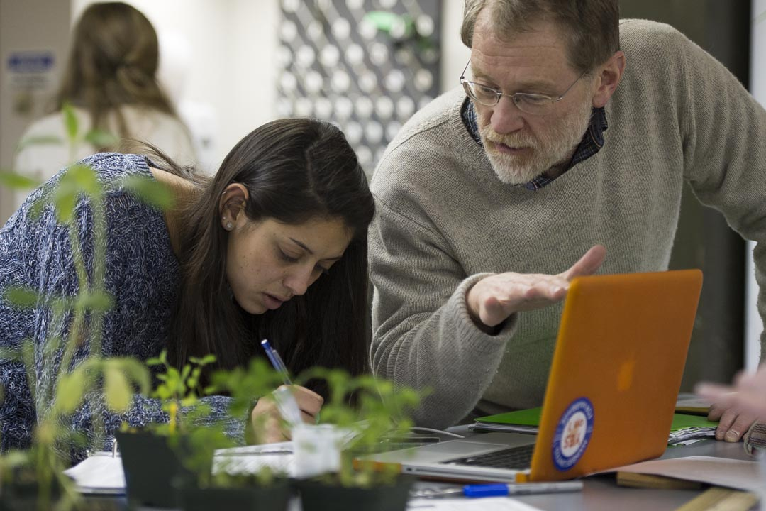 "Tara Patel '15 analyzes a plant sample during a lab session of ""Ecology and Evolution"" with Professor of Biology Will Ambrose. (Mike Bradley/Bates College)"