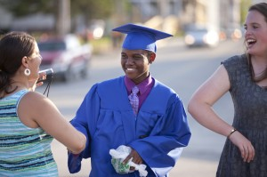 Tree Street Youth places a strong emphasis on academic achievement. Here Sleeper, left, congratulates a student upon his graduation from Lewiston High School as Sullivan, right, looks on. Photo by Phyllis Graber Jensen/Bates College.