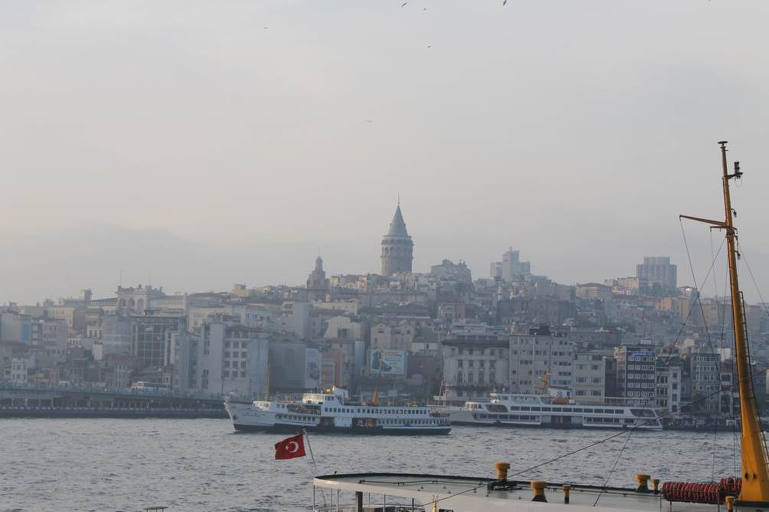 A view of Istanbul's western side taken from a boat on the Bosphorous. The Turkish flag  flies from the roof of another boat. In this part of the city high levels of pollution  cause smog that steals some of the city's beauty and triggers my allergies. Arrgh! Phillip Dube '16/Bates College.