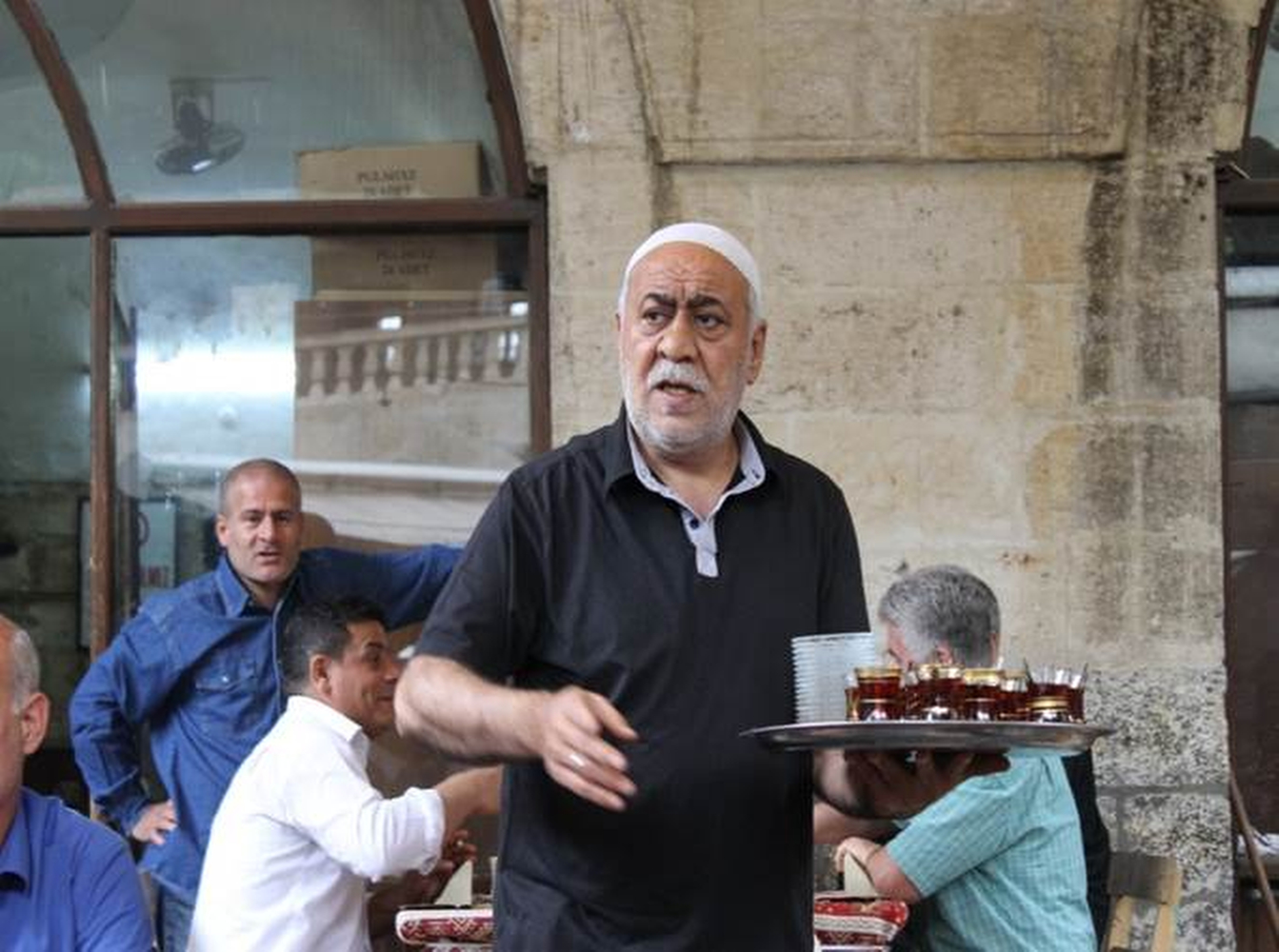 A waiter serving Turkish tea at a cafeŽ in Urfa, southeast Turkey. Cafes are places to socialize, play games and have some beverages. Phillip Dube '16/Bates College.