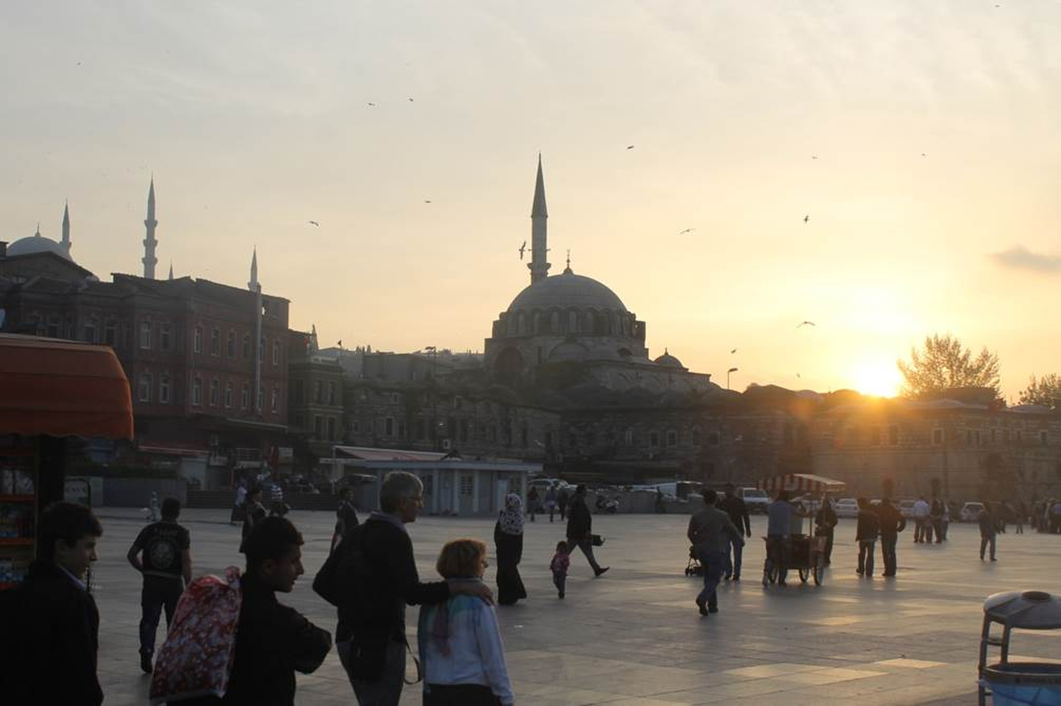 As the sun sets on Istanbul a mosque towers in the skyline  and a call for prayer emanates from the speakers on the minarets of the mosque. A street vendor sells food from his red- and white-roofed cart. Phillip Dube '16/Bates College.