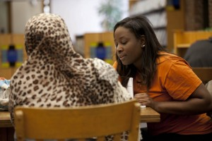 Bonner Leader Mary Osborne '13, a volunteer for the Somali Bantu Youth Organization, tutors a student in English at the Lewiston Public Library. (Phyllis Graber Jensen/Bates College)