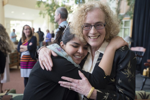 Pam Baker hugs a student during a reception for Baker's retirement on May 17, 2013. (Mike Bradley/Bates College)