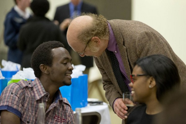 Associate Professor of English Sanford Freedman greets Desmond Mushi '13 at the Annual Senior-Faculty Dinner, held in the Gray Cage. (Phyllis Graber Jensen/Bates College)