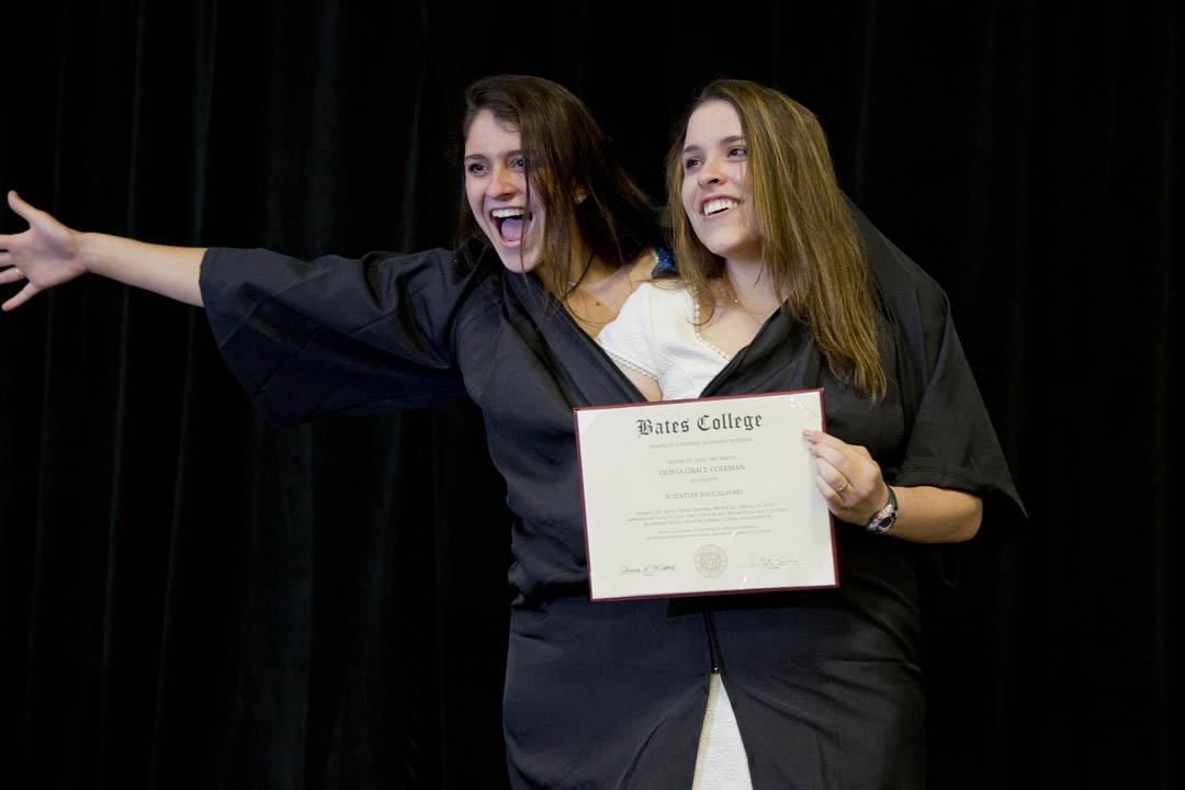 Posing for family photographers after Commencement, graduate Olivia Coleman '13, right shares her gown with sister Claire '17. (Phyllis Graber Jensen/Bates College)