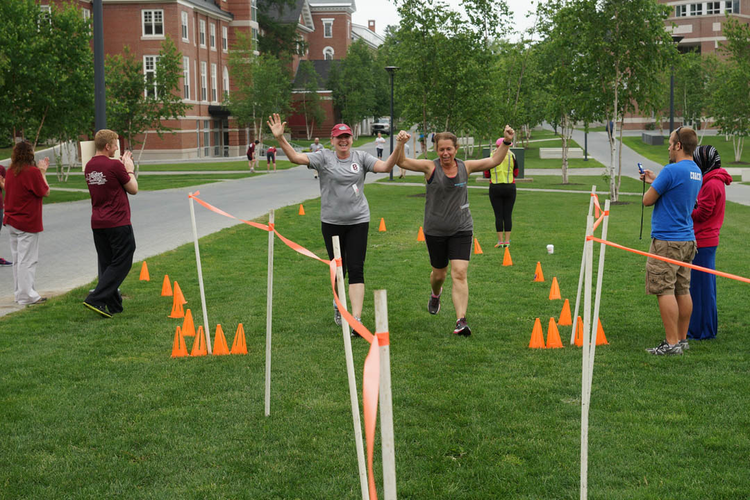 From left, Holly Lasagna of the Harward Center for Community Partnerships joins Jan Perreault  of the Office of the Registrar in crossing the finish line during the Annual B Well 5k Walk/Run for Bates employees. (Vasu Leeaphon '15/Bates College)