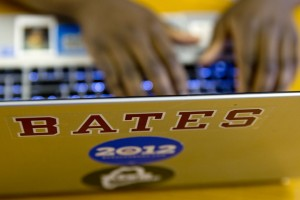 "Phillip Dube '16 of Norton, Zimbabwe, works on his laptop that he classifies as ""one of my most prized possessions."" The Bates sticker looms large because it's ""a huge part of my identity. It's four years of my life. It's going to have a big effect on who I am."" (Phyllis Graber Jensen/Bates College)"