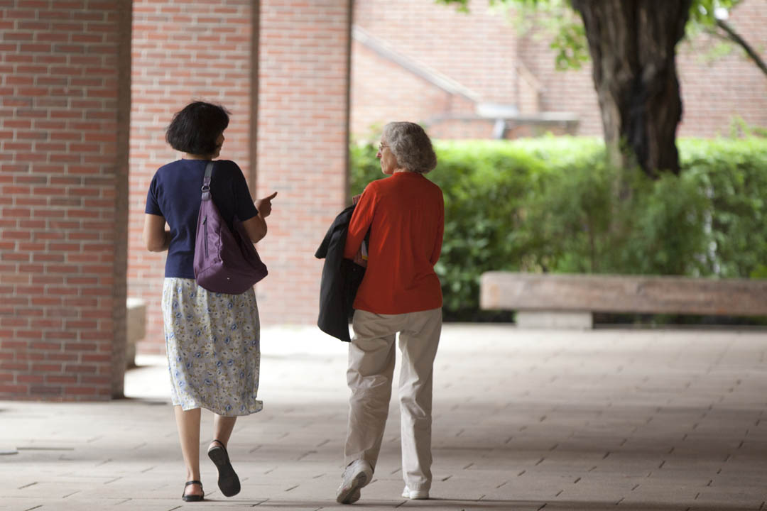 From left, Associate Professor of Mathematics Pallavi Jayawant joins Whitehouse Professor of Sociology Emily Kane for a stroll and a talk under the library arcade. (Phyllis Graber Jensen/Bates College)