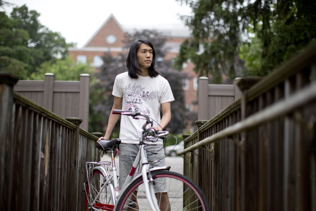 "Vasu Leeaphon '15 of Bangkok, Thailand, poses with the Schwinn that he purchased upon his arrival at Bates. ""I can go somewhere pretty fast,"" he says. (Phyllis Graber Jensen/Bates College)"
