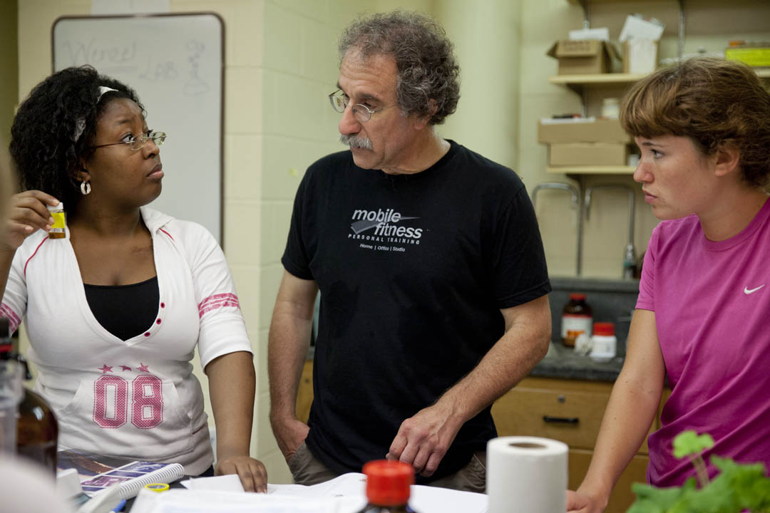 Dana Professor of Chemistry Tom Wenzel consults with, from left, Zira Mollings Puentes '16 of Kingston, Jamaica, and Mira Carey-Hatch '14 of Laconia, N.H. They are synthesizing novel cavity compounds that can be used to distinguish pharmaceutical compounds with right- and left-handed forms.   (Phyllis Graber Jensen/Bates College)