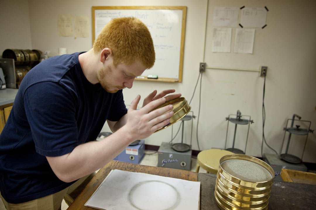 In Carnegie Science, geology major Chris Halsted '14 of Lincoln, Mass., examines specimens gathered during a Short Term trip to Scotland's Shetland Islands for his NSF-funded study of the burial of a 17th-century settlement by windblown coastal sand. (Phyllis Graber Jensen/Bates College)