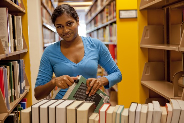 Andria T.  Bhagwandeen '15 shifts and cleans the stacks in the Ladd Library.