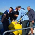 Lake Auburn Watershed Protection staffers and environmental studies professor Holly Ewing (pale blue jacket) prepare to place a sensor buoy in  Lake Andrews. Kate Paladin '15/Bates College.
