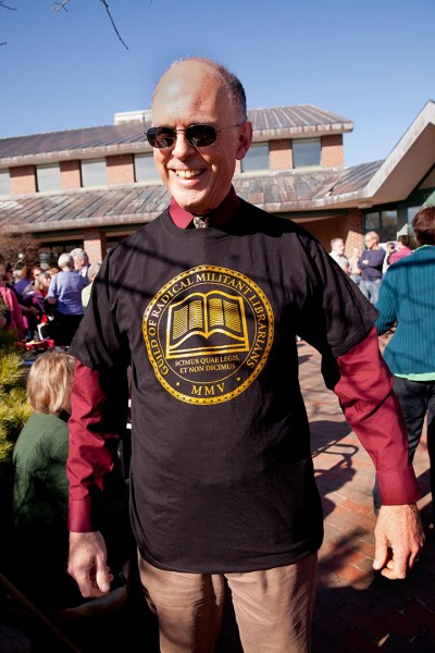 """At his reception last spring, Tom Hayward wears a librarian-themed T-shirt given to him by classics students. The Latin """"Scimus quae lemis, et non dicimuc"""" means """"We know what you read and we don't tell."""" (Phyllis Graber Jensen/Bates College)"""