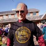 "At his reception last spring, Tom Hayward wears a librarian-themed T-shirt given to him by classics students. The Latin ""Scimus quae lemis, et non dicimuc"" means ""We know what you read and we don't tell."" (Phyllis Graber Jensen/Bates College)"