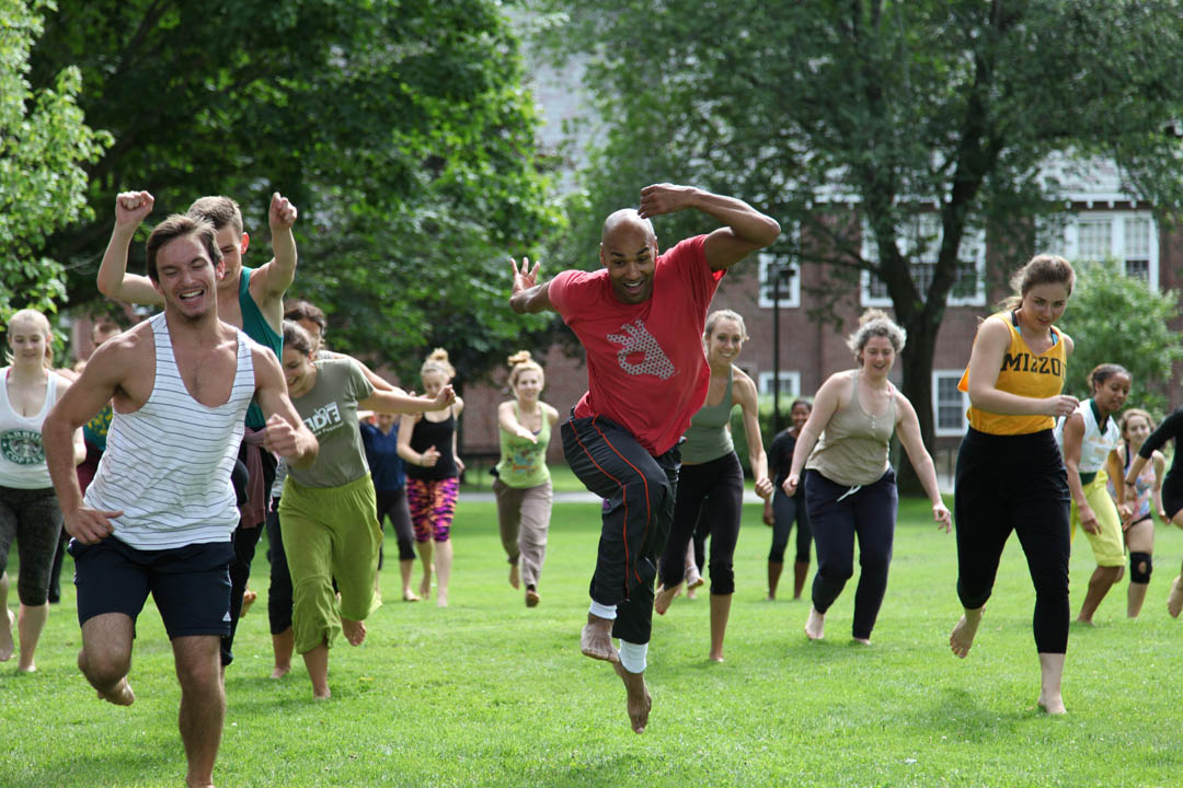 Darrell Jones (center), a veteran member of Bebe Miller Company, leads a Bates Dance Festival level-4 modern dance class on the Ladd Library Quad. (Marc Glass/Bates College)
