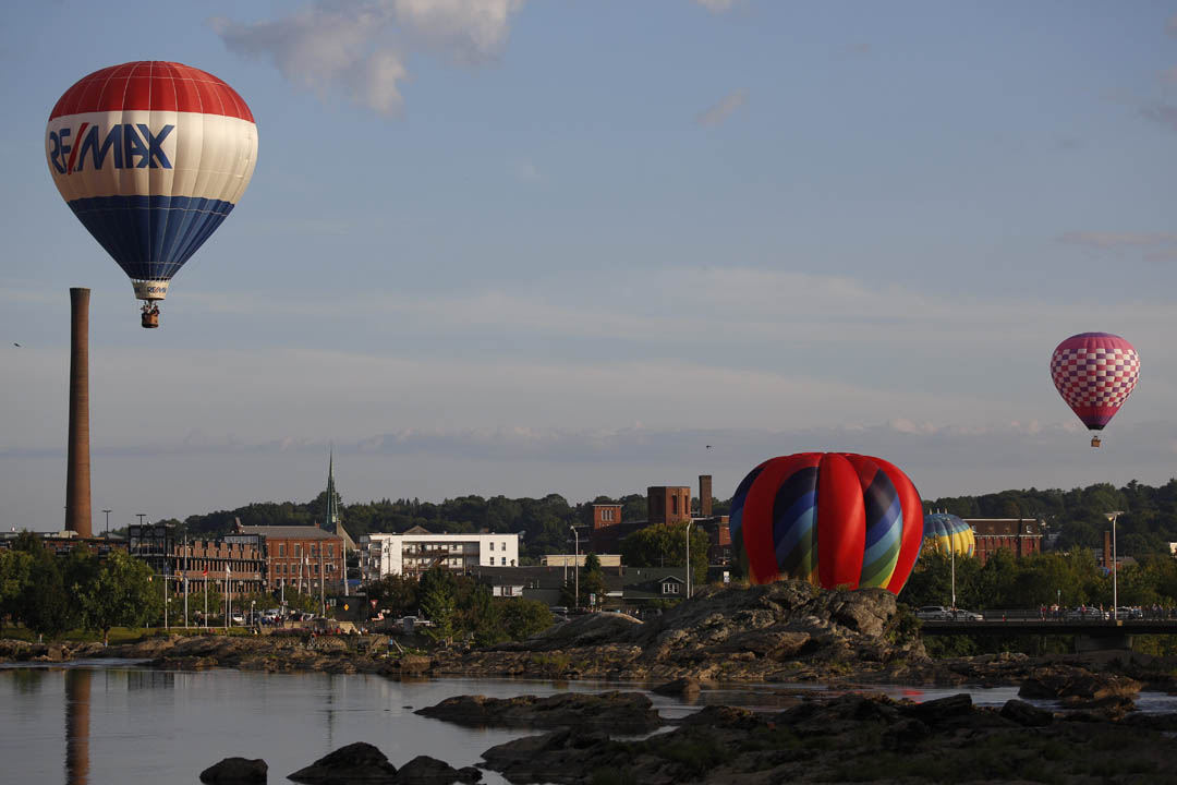 Hot air balloons fly above Lewiston and Auburn during the Great Falls Balloon Festival. (Mike Bradley/Bates College)