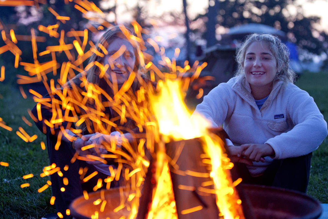 After a day of working with the Ellsworth, Maine, chapter of Habitat for Humanity, AESOP leader Abby Knudsen '16 of New York City (left) enjoys a campfire in Sullivan with Olivia Voccola '17 of Falmouth, Maine. (Phyllis Graber Jensen/Bates College)