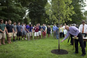 Head football coach Mark Harriman pours water from Lake Andrews on a tree planted at a post-Convocation memorial service for members of the Bates community who died in the previous year . Troy Pappas '16, a freshman on Harriman's team, died in October 2012. (Phyllis Graber Jensen/Bates College)