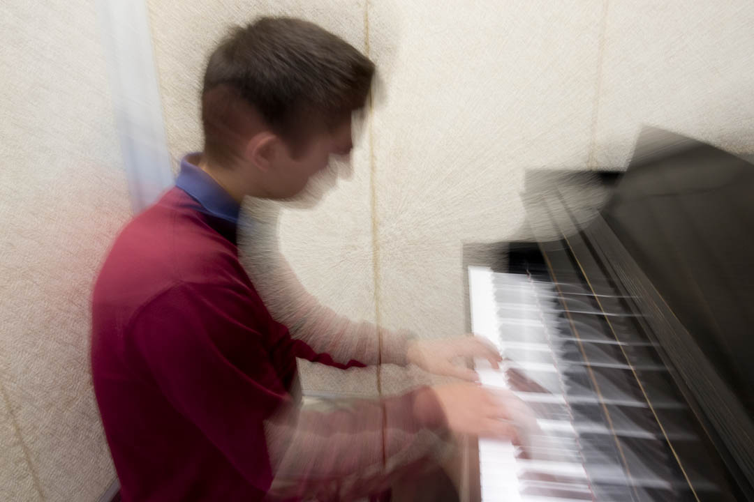 Matthew Moss-Hawkins' 17 of Newton, Mass., has just a few minutes before class to duck into an Olin Arts Center rehearsal room to play the piano. (Phyllis Graber Jensen/Bates College)