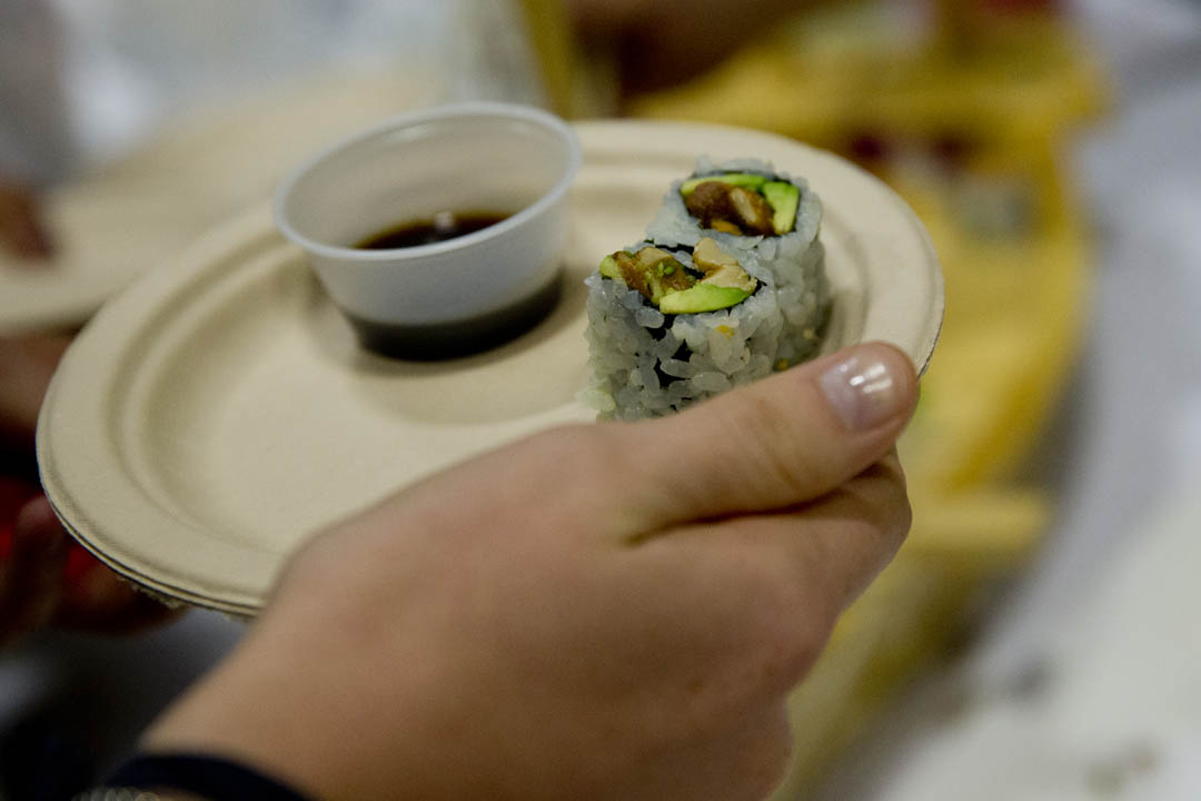 A student samples sushi in the Gray Cage during the Office of Student Activities-sponsored Ninth Annual Taste of Lewiston-Auburn, featuring mouth-watering cuisine from area restaurants. (Phyllis Graber Jensen/Bates College)